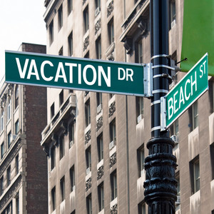 A sign post at the intersection of two streets reading VACATION DR and BEACH ST.  Remove the words and insert your own to easily customize the message.