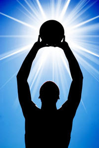 A silhouette of a basketball player holding up a ball in front of a bright glowing lens flare.