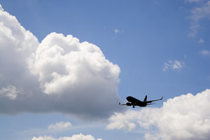 A silhouette of a commercial passenger plane over a blue sky in its descent to land.