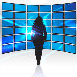 A silhouette of a woman standing in front of a wall of tv screens.