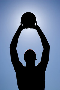 A silhouette of a young basketball player holding the ball up to the sky.