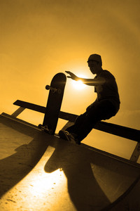 A silhouette of a young skateboarder at the top of a ramp at the skate park.