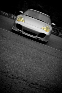 A silver sports car with the yellow headlights highlighted in selective color.  Plenty of copyspace for your text.