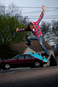 A skateboarder performing jumps or ollies on asphalt.  Slight motion blur showing the movement on the arms and legs.