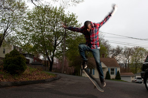 A skateboarder performs jumps or ollies on asphalt.  Slight motion blur showing the movement on the arms and legs.