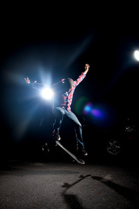 A skateboarder performs tricks under dramatic rim lighting with lens flare.