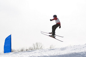 A skier catching some major air after launching off of a jump.