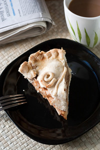 A slice of fresh homemade deep dish apple pie on a plate with a hot coffee and the newspaper.  The perfect desser or breakfast.  Shallow depth of field.