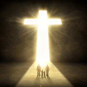 A small family walks together to the glowing cross