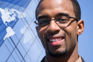A smiling African American man over a world map conceptual background.