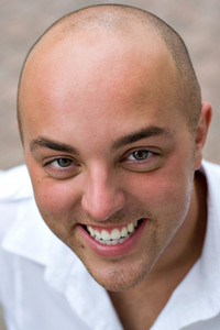 A smiling young bald man up close.  Shallow depth of field.