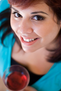 A smiling young woman holding a glass of red wine. Shallow depth of field with focus on the eyes.