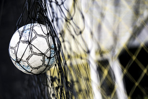 A soccer ball stuck on the net behind goal