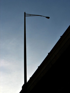 A street lamp as seen from below a highway overpass.