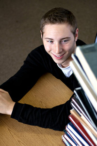 A student happily looks up at the high pile of textbooks he has to go through to do his homework assignment.