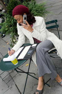 A successful career woman conducting business outdoors at a table with her cell phone and coffee.