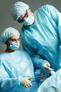 A surgeon and a nurse operating on a patient