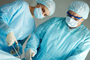 A surgeon and a nurse operating