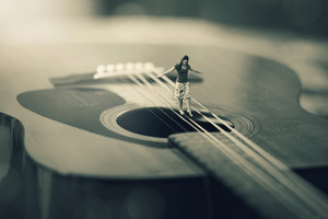 A surreal image of a woman balancing on strings of a guitar
