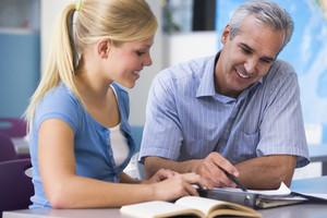 A teacher instructs a schoolgirl in a high school class