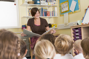 A teacher reads to schoolchildren in a primary class