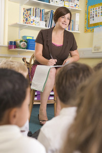 A teacher sits with schoolchildren in a primary class