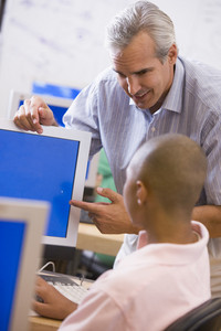 A teacher talks to a schoolboy using a computer in a high school class