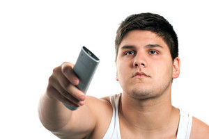 A teenager changes the channel with the remote control isolated over a white background. Shallow depth of field.