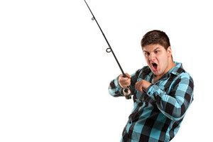 A teenager is surprised as he reels in a big fish.  Isolated over white in studio with plenty of negative space.