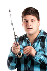 A teenager is surprised as he reels in a big fish.  Isolated over white in studio.