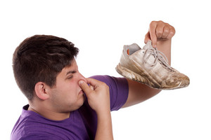 A teenager pinches his nostrils closed over the odor given off from the athletic shoe he is holding.