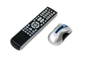 A television remote control and a wireless computer mouse both isolated on white.