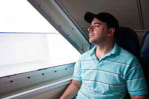 A tired looking passenger seated on a ferry boat looks out the window as he awaits arrival to his destination.