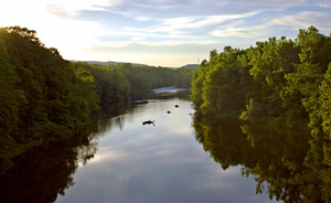 A view of the beautiful Farmington river in Connecticut.  Fly fishermen are wading in the water in the distance.
