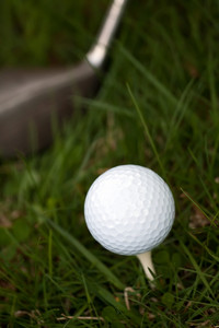 A white golf ball set up on the tee with a driver about to swing.  Shallow depth of field.