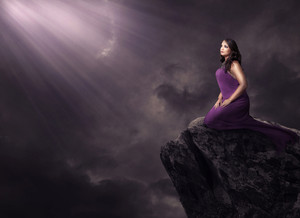 A woman alone on a cliff under glowing lights