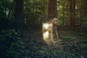 A woman climbs out of a picture frame into a forest