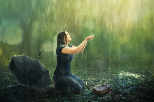 A woman enjoys a rain shower in the forest.