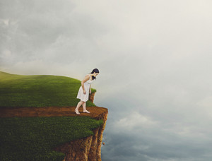 A woman gets to the end of the pathway and looks over the edge
