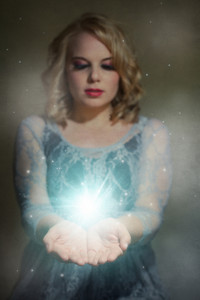 A woman has her hands out and holding a glowing orb