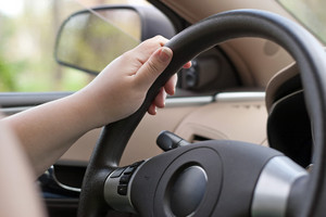A woman holding the steering wheel of a car with one hand while driving.