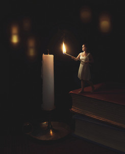 A woman holds a match to light a candle