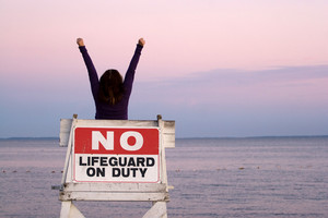 A woman holds her arms up in the air while seated in a vacant lifeguard chair at the beach.