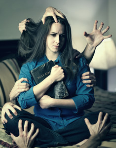 A woman holds her Bible as many hands grab her