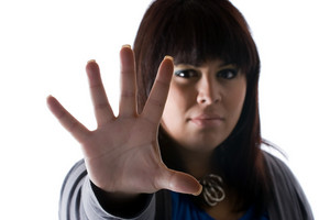 A woman holds up the palm of her hand in a defensive manner.  Shallow depth of field.
