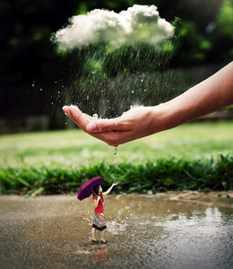 A woman in a rain shower is being protected by a large hand