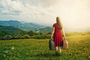 A woman in a red dress carries her luggage into the mountain landscape.