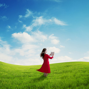 A woman in a red dress is reading her Bible in a field