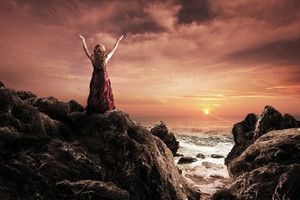 A woman in a red dress praising at the ocean