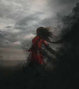 A woman is being grabbed by dark clouds and smoke